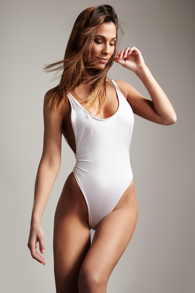 beauty perfect fit spanish woman in white swimsuit and flying hair in air