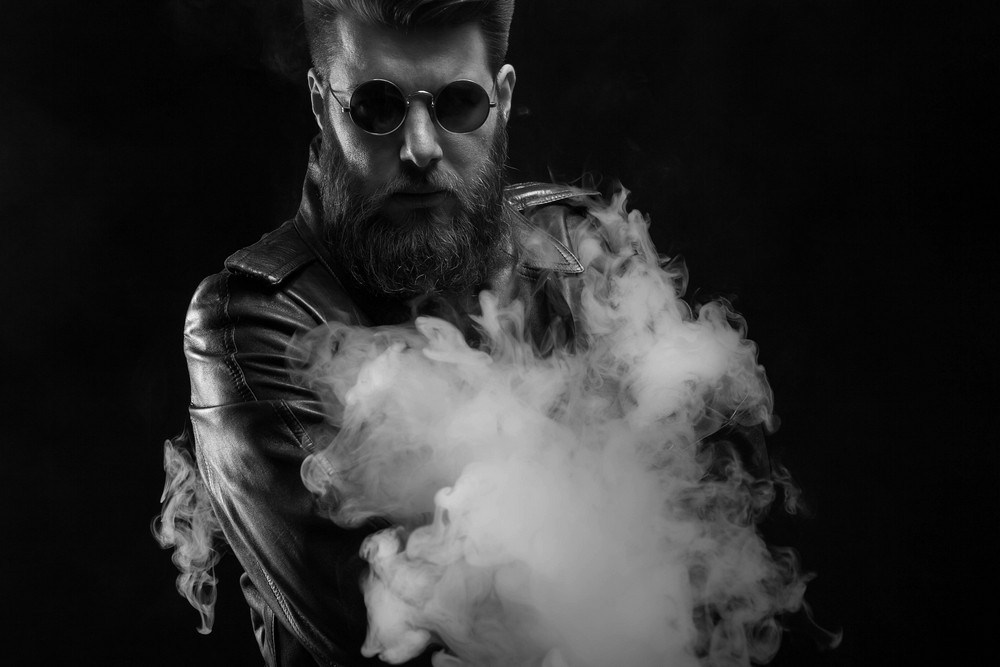 Black and white portrait of serious man wearing a leather jacket in studio photoshoot over black background. Stylish beard. Serious man.