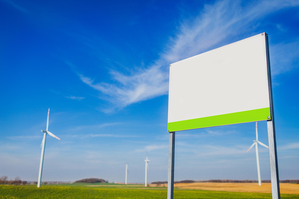 Blank board on area with energy windmills