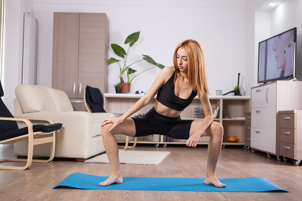 Blonde young womna doing Goddess yoga pose during her training. Health lifestyle training.