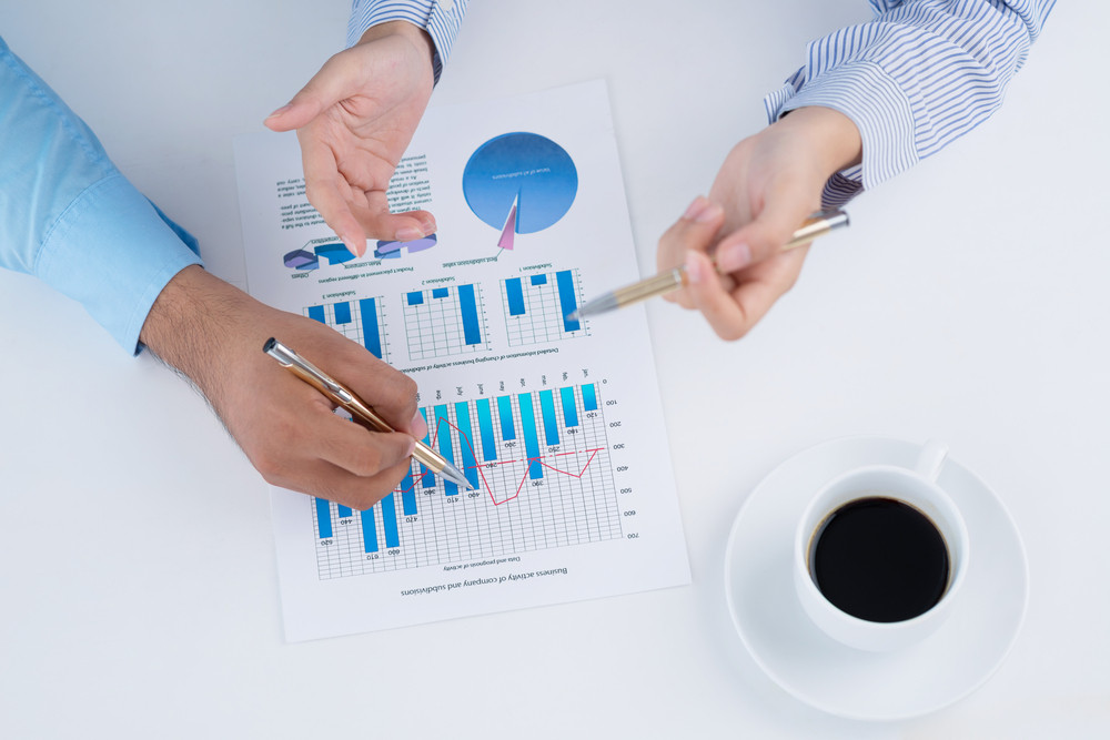 Business colleagues discussing the financial graphics viewed below