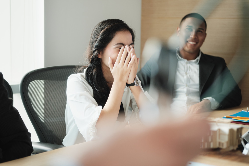 Business people during conference. Team of African american businessman and Asian businesswoman laughing and having fun at meeting in room with manager telling jokes.