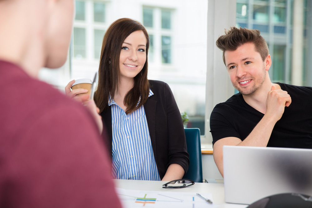 Business People Smiling While Looking At Colleague At Desk