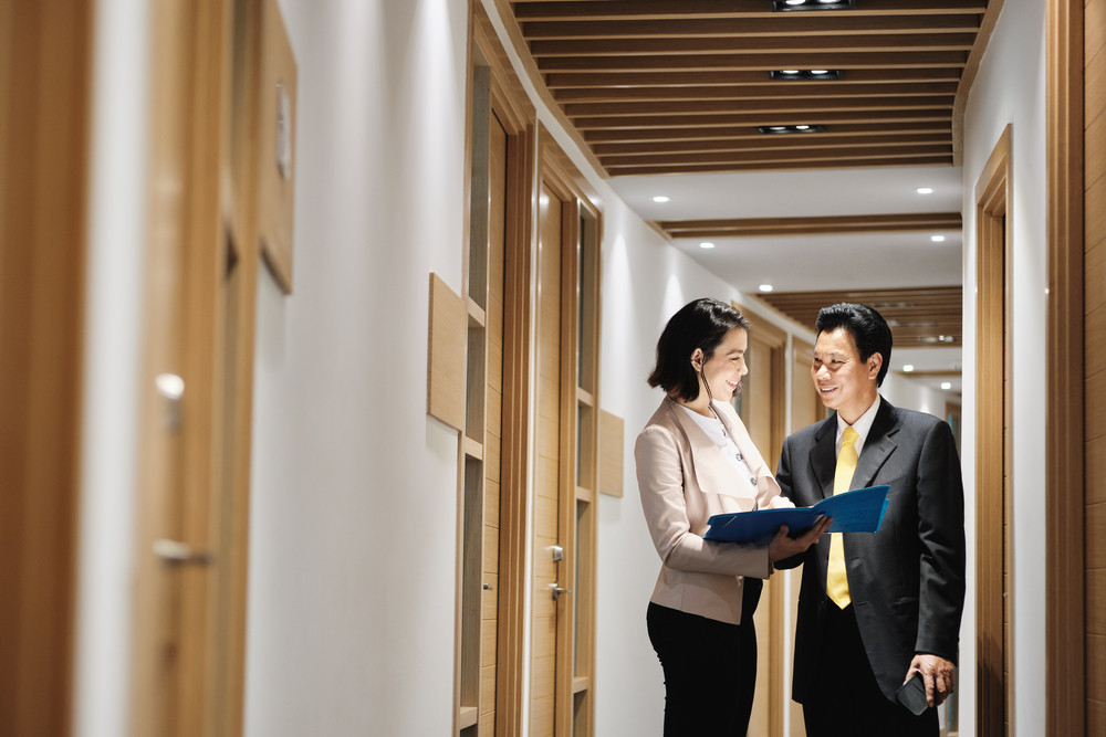 Business woman at work as advisor in office, talking with client in corridor. Health insurance broker meeting Chinese client, retirement plan agent explaining agreement to Asian manager