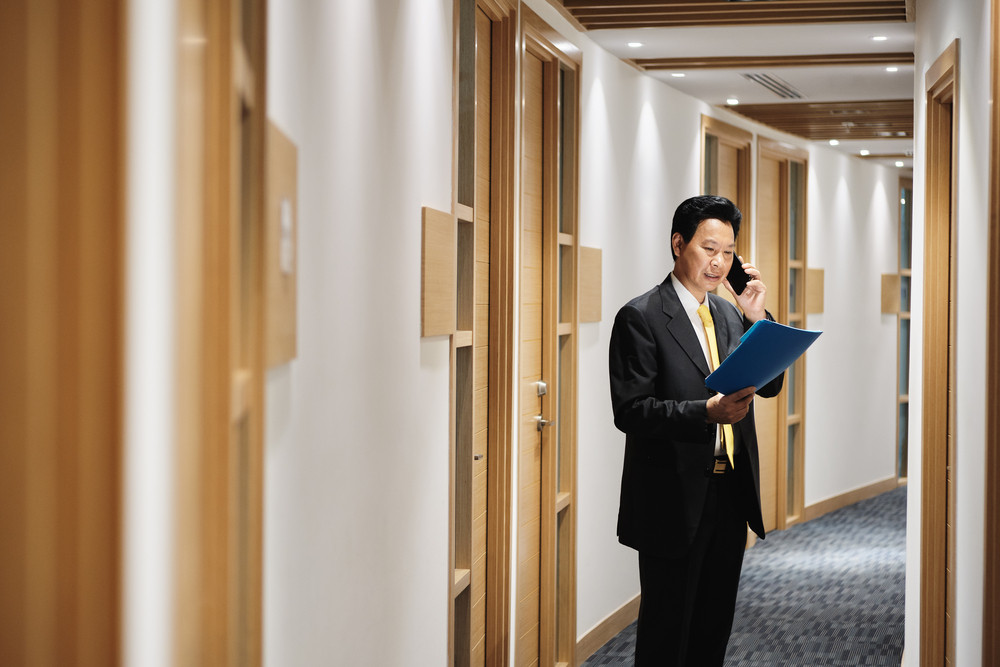 Businessman working as advisor in office, financial consultant talking on mobile telephone. Happy bank manager speaking with smartphone, Asian business man explaining contract to client on the phone