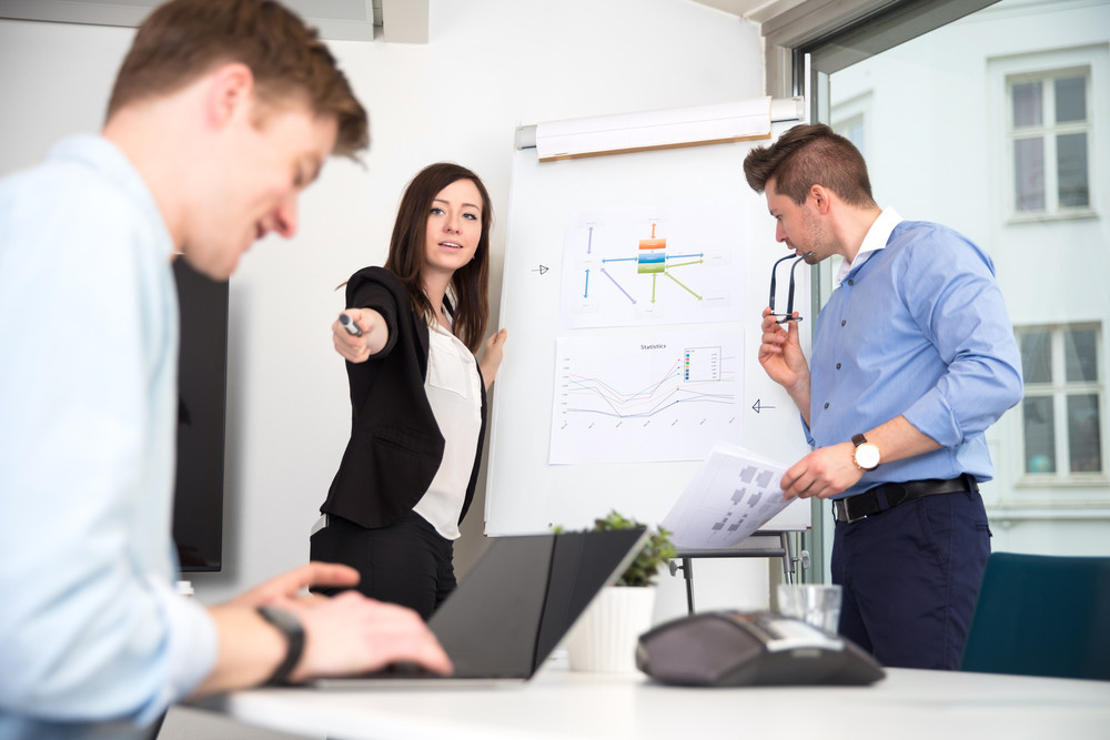 Businesswoman Pointing At Male Colleague Using Laptop