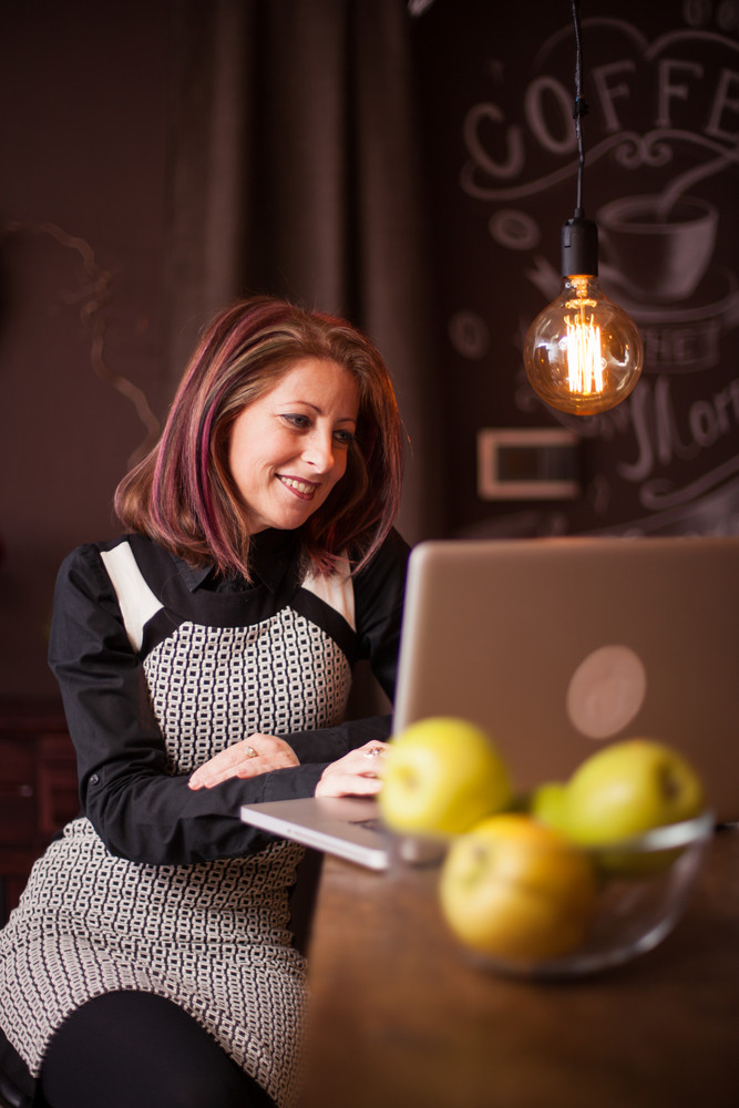 Businesswoman smiling while looking at her laptop in a vintage coffee shop. Enjoying herself while sitting at bar counter