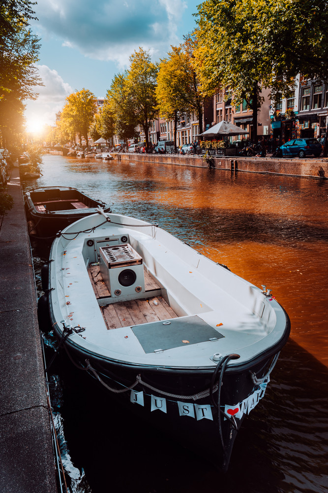 Channel in Amsterdam at autumn sunset. Boat in front of tree-lined canal, white clouds in the sky. Netherlands houses landmark landscape. Romantic City trip concept