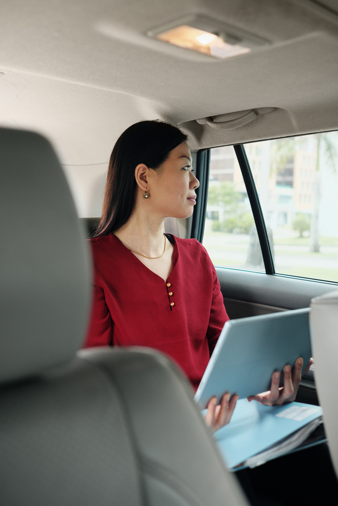 Chinese female manager working in car while commuting to work. Successful Asian businesswoman using laptop computer and riding taxi, busy woman sitting in cab and going to office