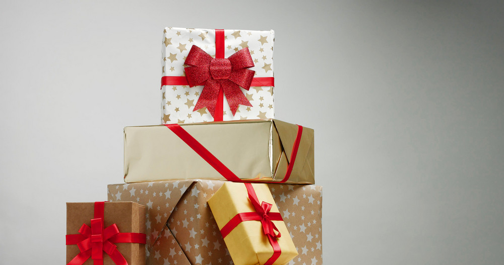 Christmas present in boxes with beautiful paper and ribbons piled up gradually isolated on white