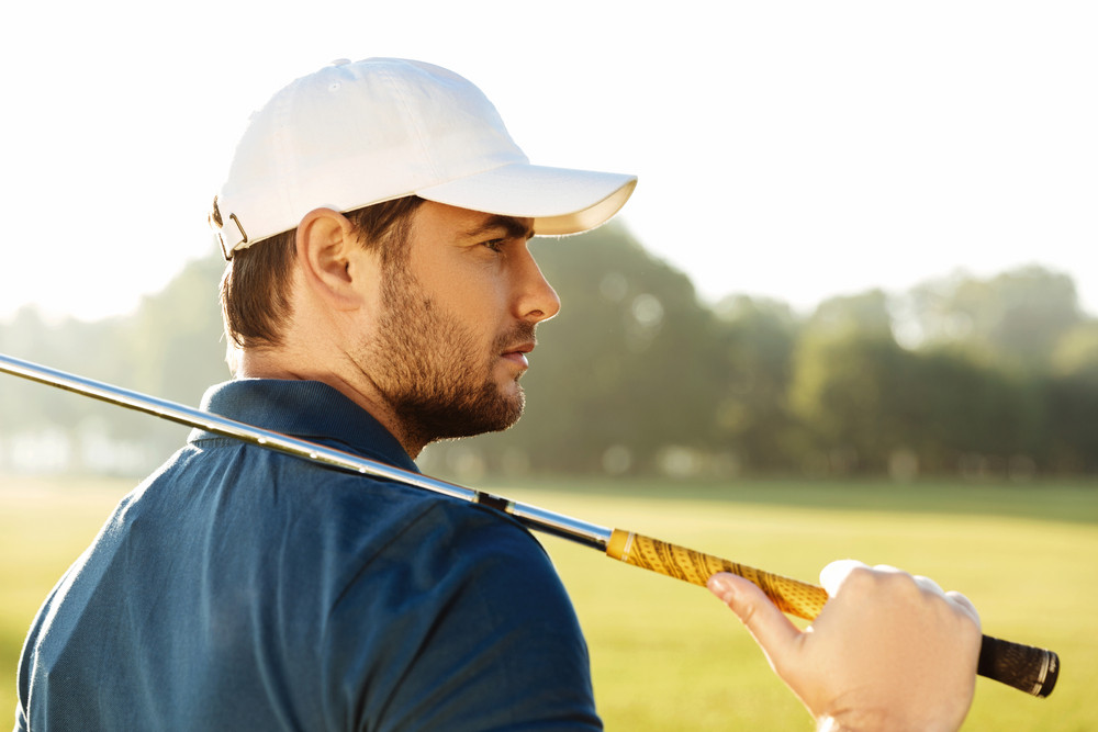 Close up of a young handsome male golfer in hat holding golf club and looking away