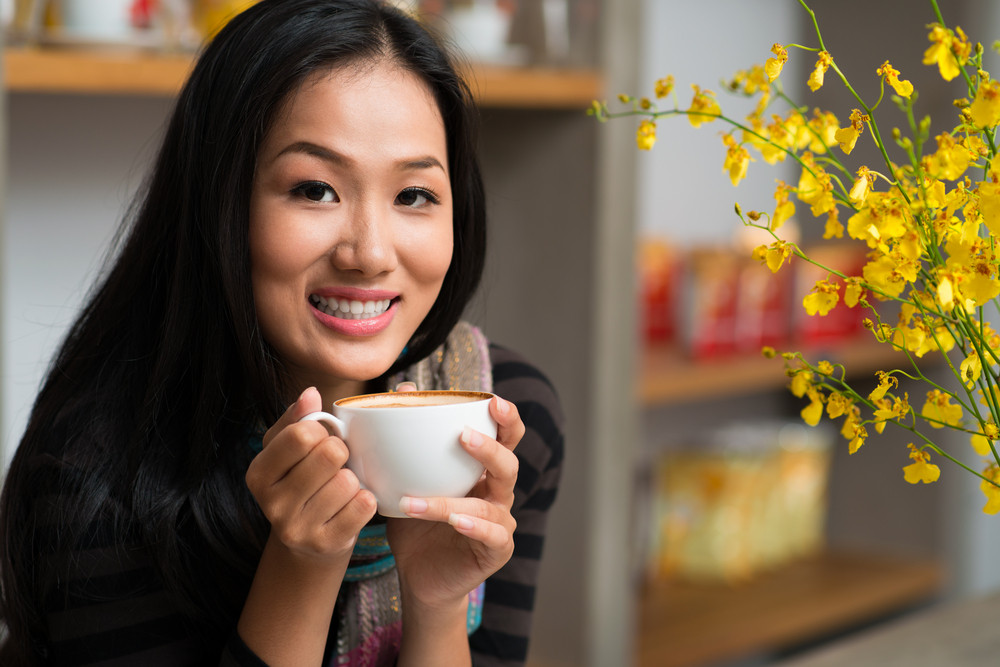 Close-up portrait of a young lovely lady with a latte cup in hands