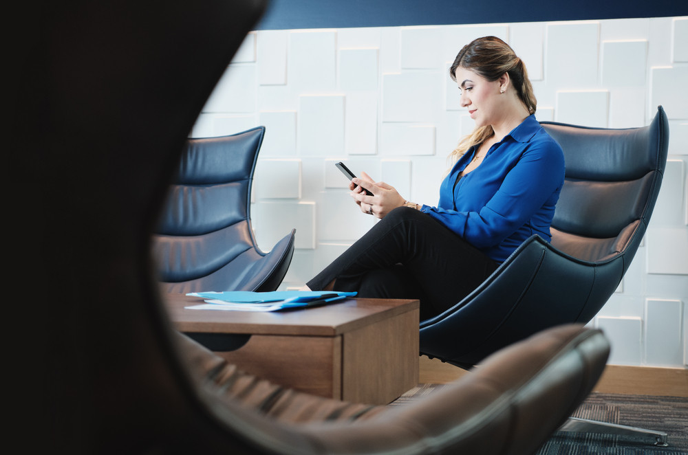 Concentrated business woman working with mobile phone in office waiting room, hispanic lady typing text message on social media on smartphone.