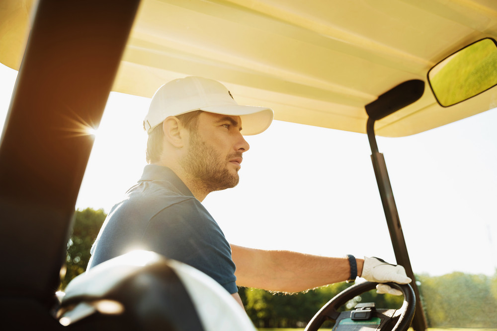 Concentrated male golfer driving a golf cart