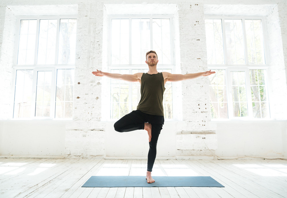 Concentrated young man parctising yoga pose on a fitness mat indoors