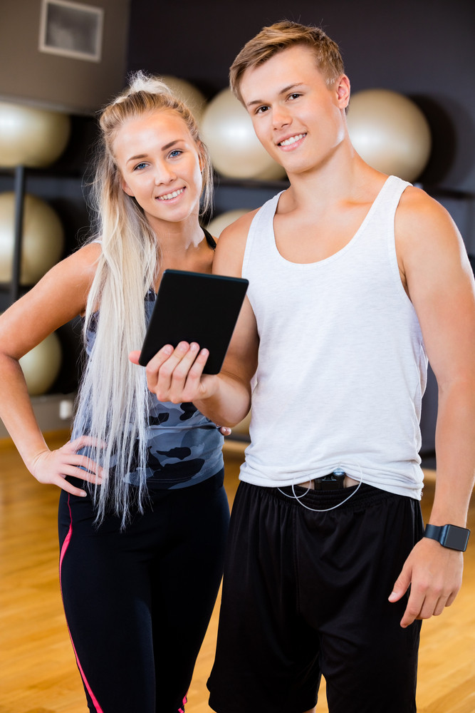Confident Man And Woman With Digital Tablet In Gym