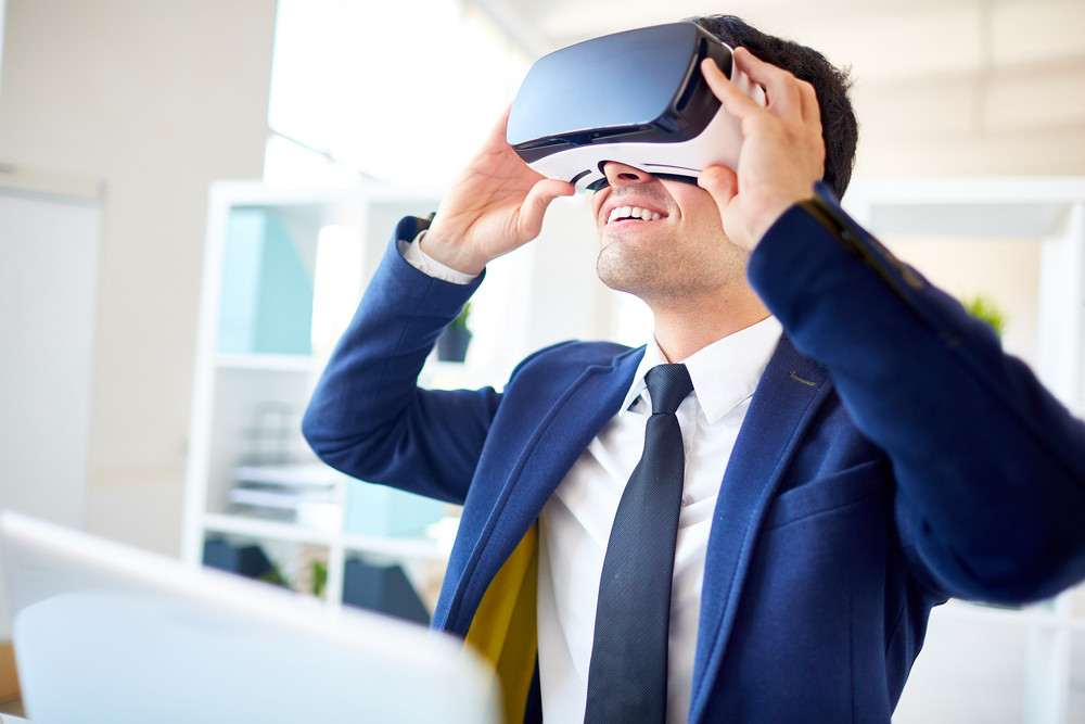 Contemporary businessman with 3d goggles watching curious game or video by workplace