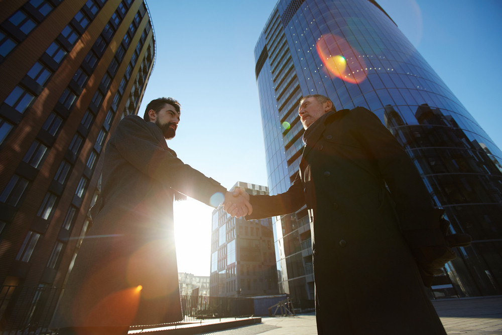 Contemporary employers handshaking outdoors between two skyscrapers