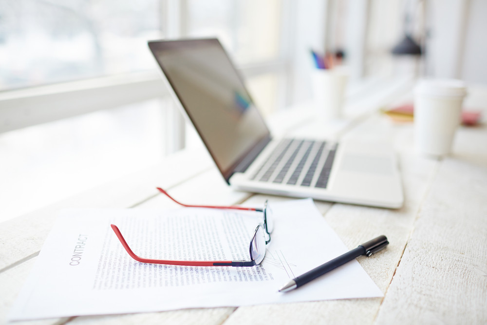 Contract, pen, eyeglasses and laptop on workplace