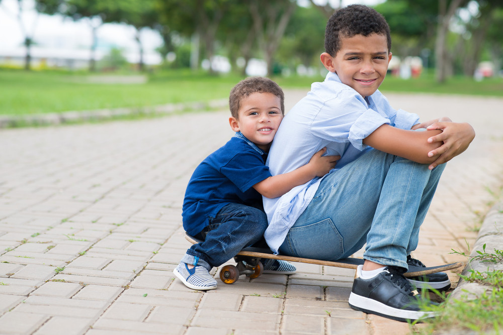 Copy-spaced portrait of brothers sitting on the skateboard in the park