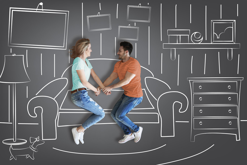 Couple holding hands against furniture background