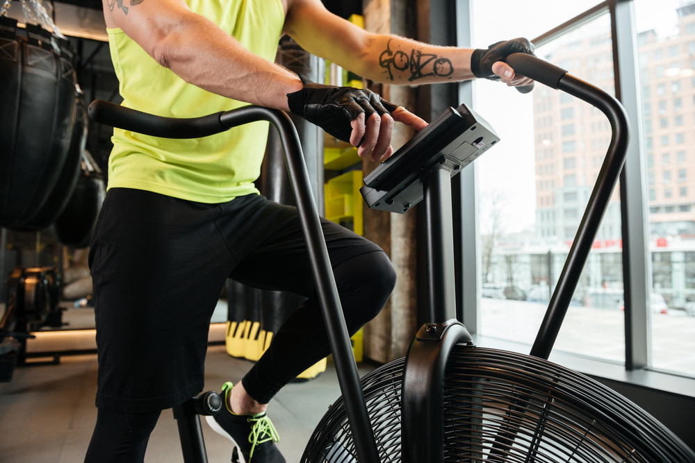 Cropped image of a sportsman doing exercises on a treadmill at the gym