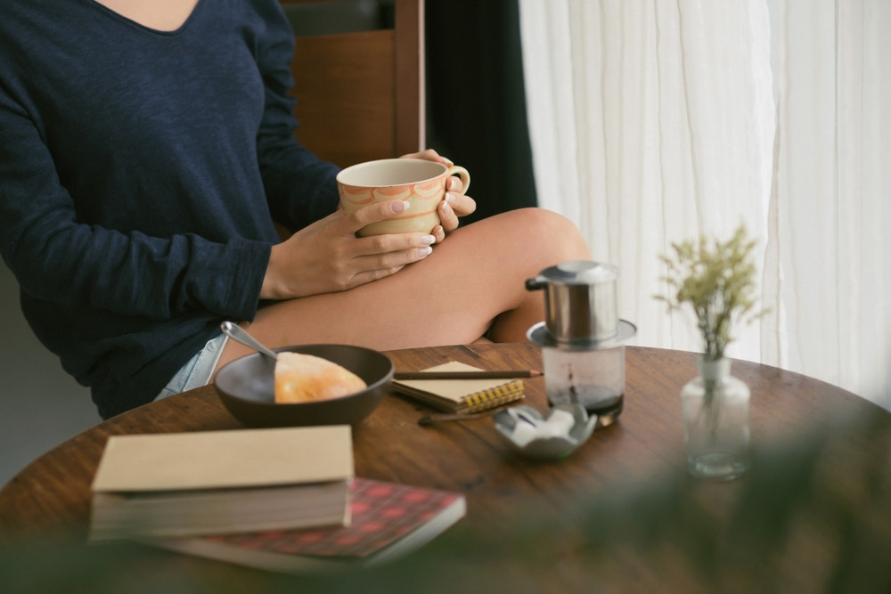 Cropped image of girl sitting at the table and drinking tea