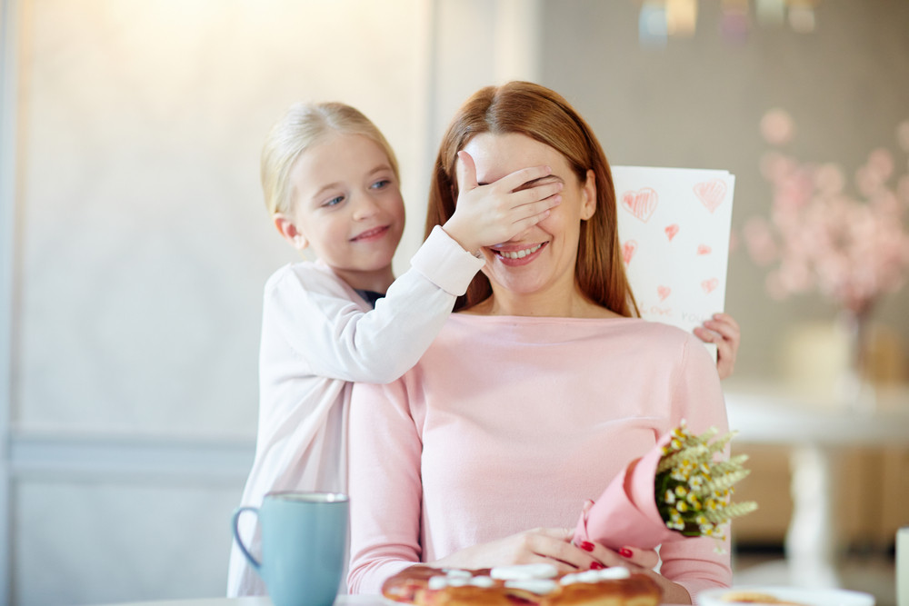 Cute child covering her mother eyes before surprise