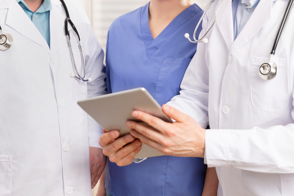 Doctor and medical team discussing patient report at tablet computer in hospital