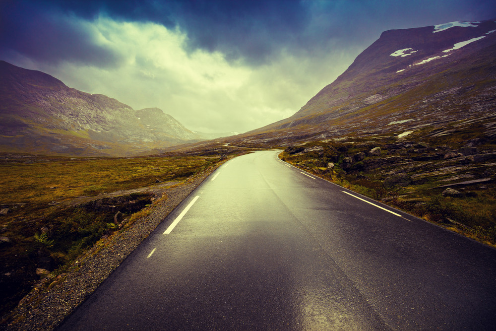 Driving a car on mountain road. Road among mountains with dramatic stormy cloudy sky landscape.  Beautiful nature in Norway
