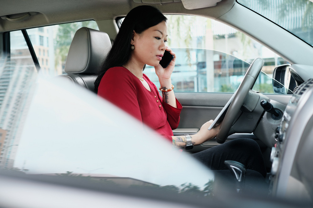 Efficient Chinese female manager working in car. Successful Asian businesswoman smiling and talking on cell phone, busy woman sitting in car and using computer