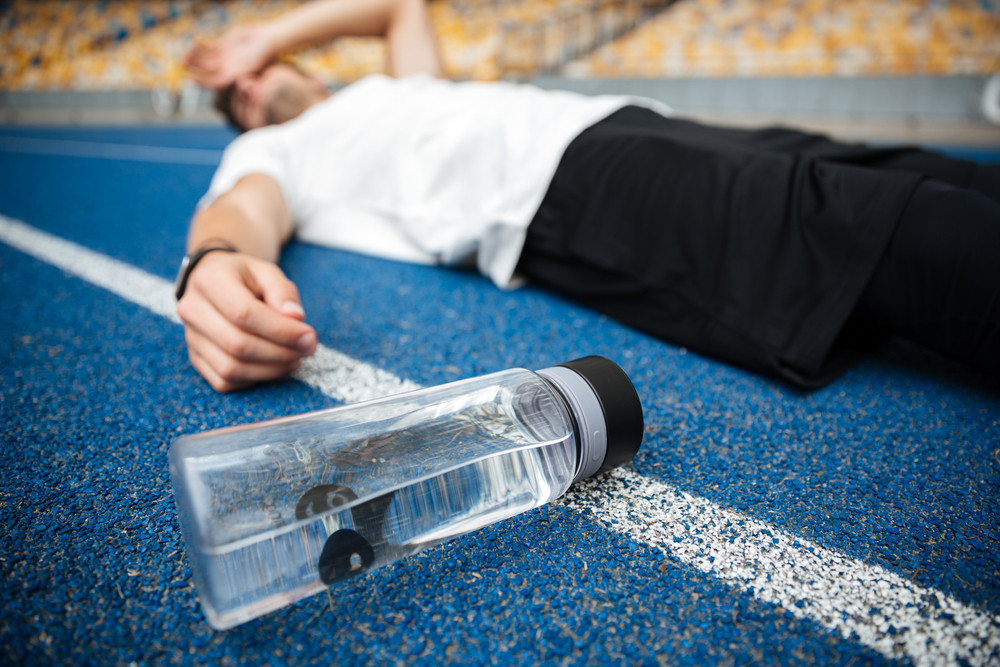 Exhausted young sportsman lying on a racetrack with bottle of water at the stadium