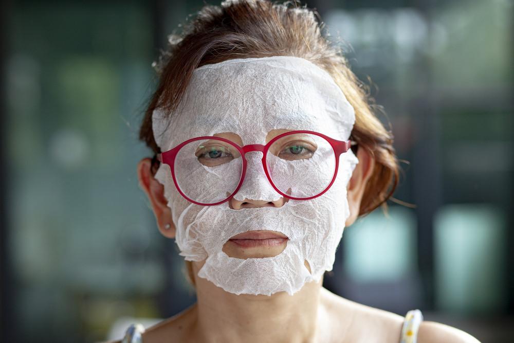 face of woman making face skin tretment masking