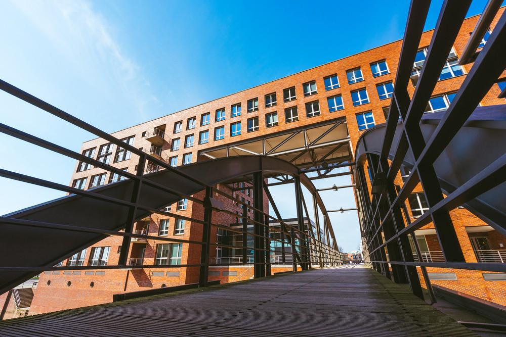Famous landmark old Speicherstadt in Hamburg, build with red bricks. Bridge in low angle view.