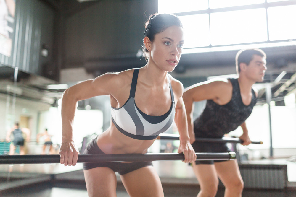 Female athlete exercising with fitness bar