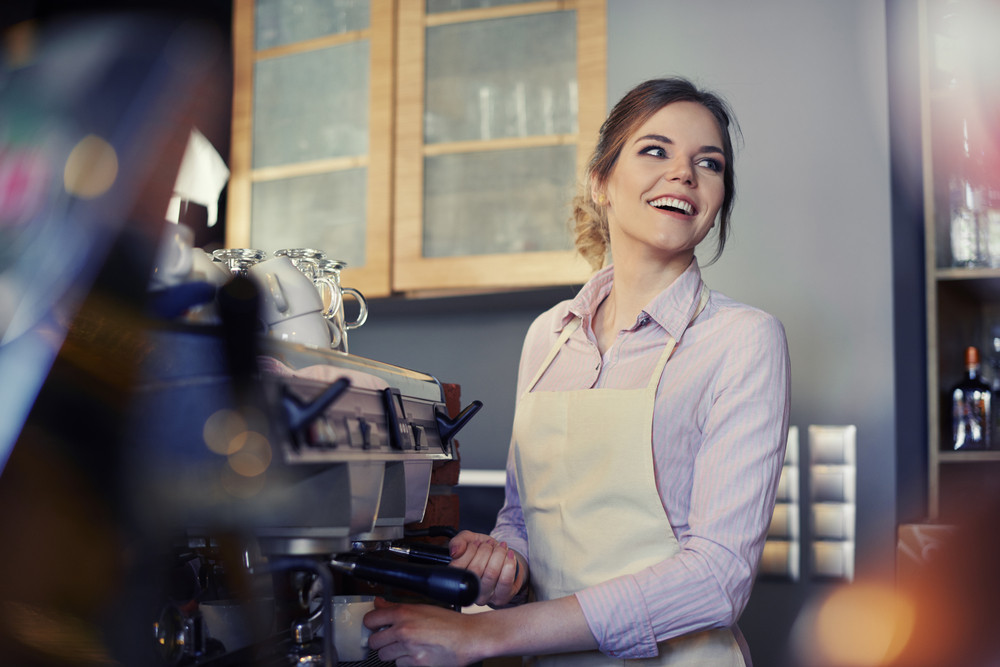 Female barista using coffee maker in cafe
