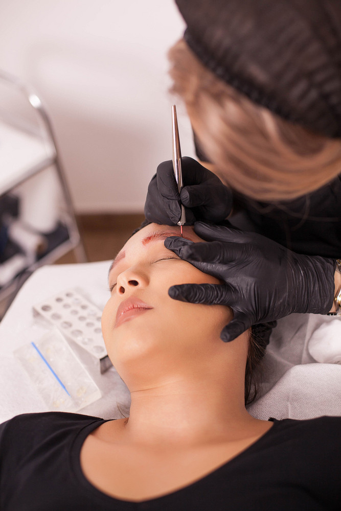 Female beautician using modern technology for tattoo removal. Medical procedure. Female patient. Hygiene procedure.