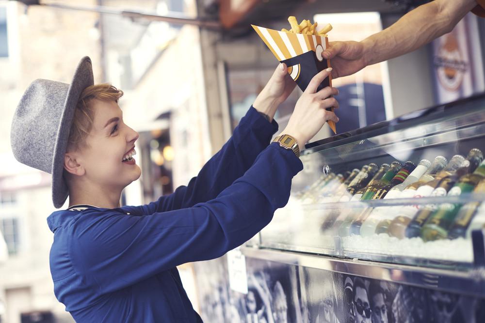 Female customer reaching food from vendor