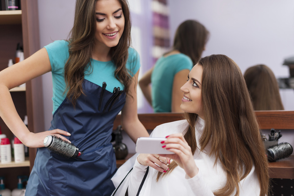 Female customer showing which hairstyle she wants on mobile phone