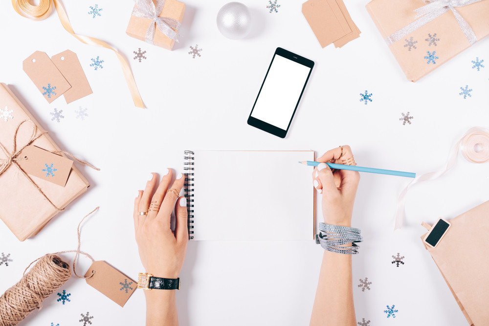 Female hand writing in a notebook shopping list on white table among the Christmas decorations, top view