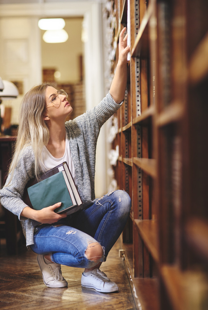 Female student searching a book in library