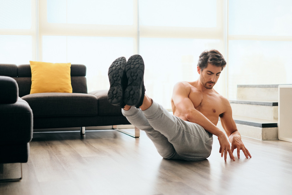 Fit young white man training at home. Handsome hispanic male athlete working out for wellbeing in domestic gym, training abdomen with Russian twist exercise