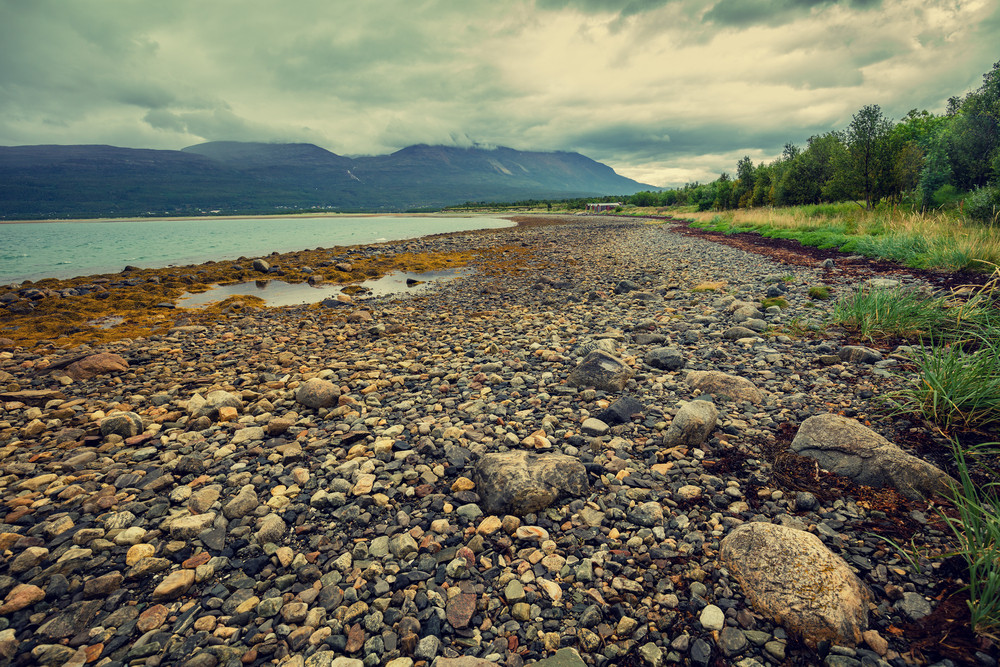 Fjord in stormy weather.  Rocky beach. Norway