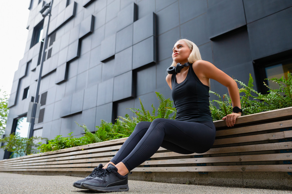 Focused Woman Doing Triceps Dips Outdoor in the City