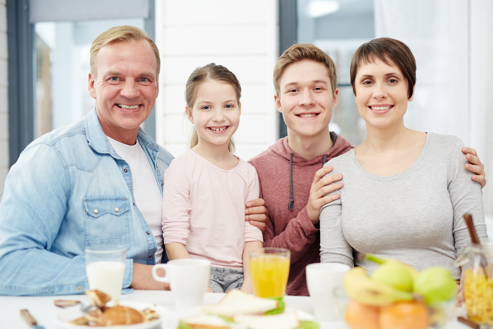 Four family mambers sitting by table with organic food