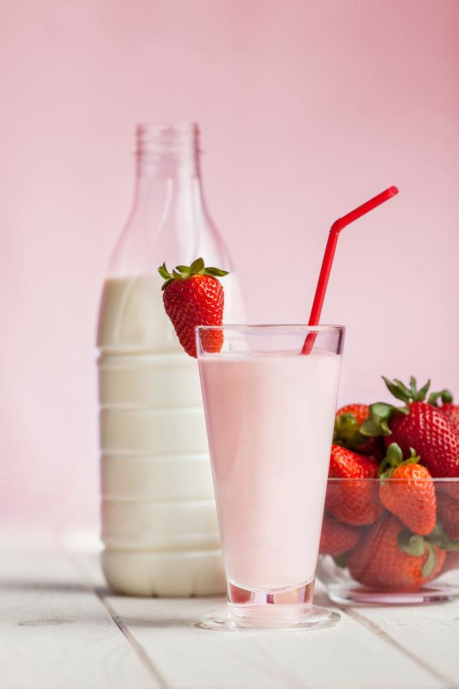 Fresh strawberry milk shake on wood