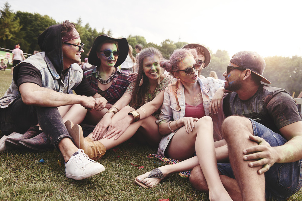 Friends sitting on the grass at music festival