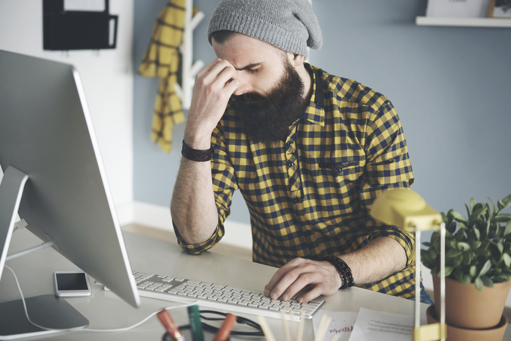 Frustrated young man at computer desk