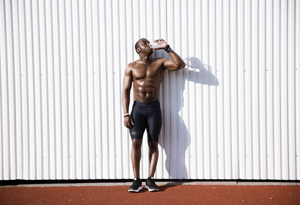 Full length of a sporty african male athlete drinking from a water bottle while standing against white wall