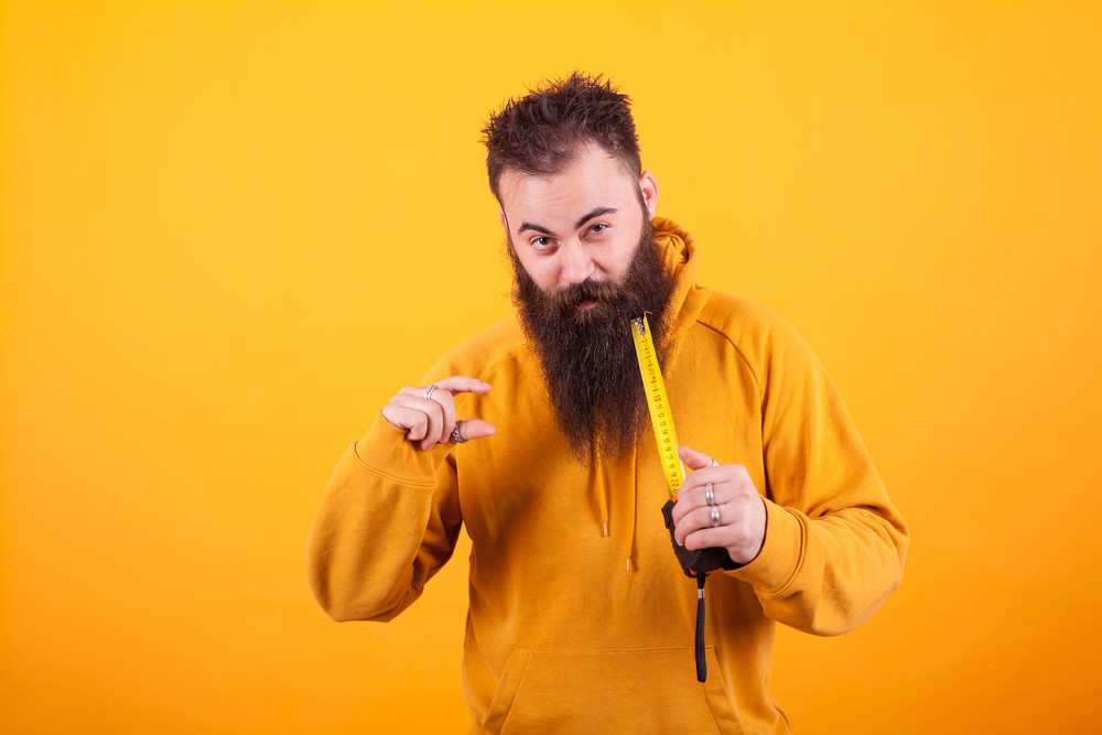 Funny bearded man showing dimension on roulette over yellow background. Handyman. Constructor